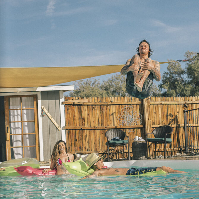 Friends cool down and float in a pool wearing Fox Racing boardshorts. Shop for your new pair now